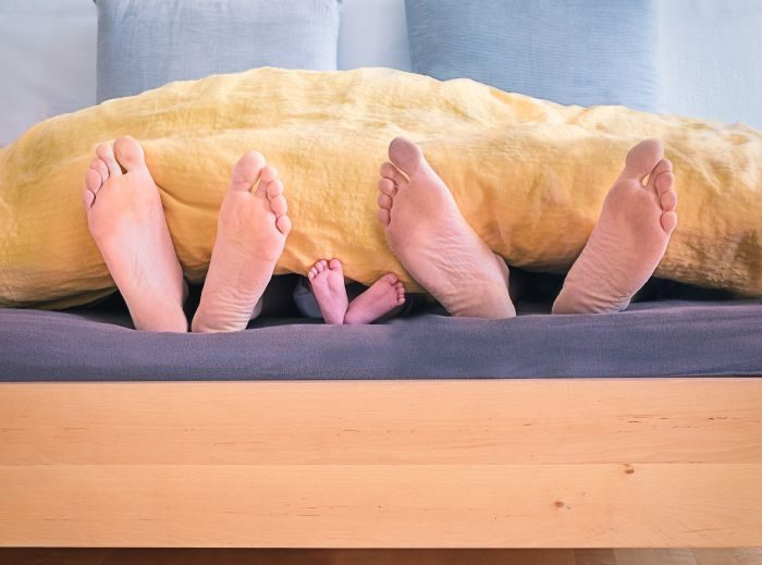 picioare de adulti si de copil care ies de sub plapuma