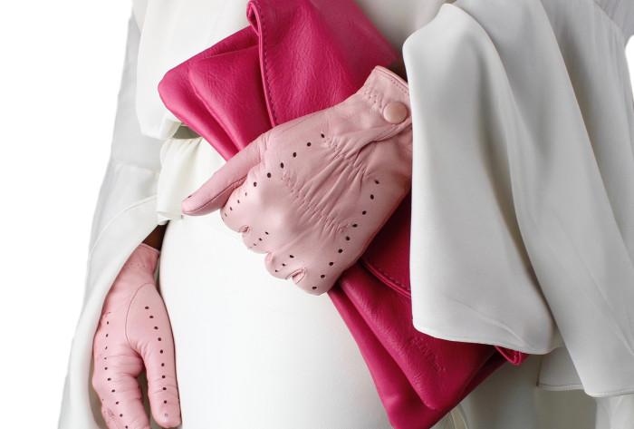 femeie eleganta care poarta manusi din piele de culoare roz si o geanta plic fucsia