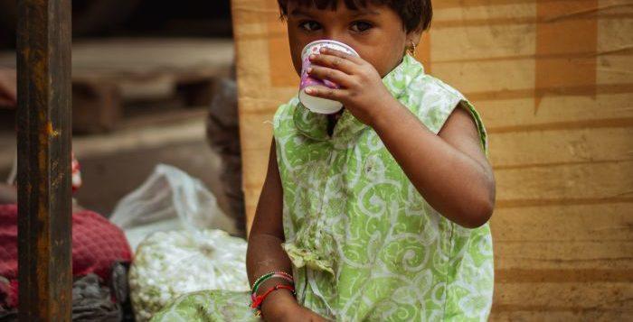 Copil sărman care stă pe jos și bea dintr-un pahar