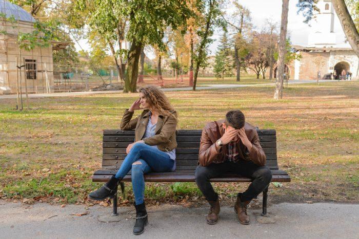 cuplu femeie si barbat care stau pe o banca si se cearta