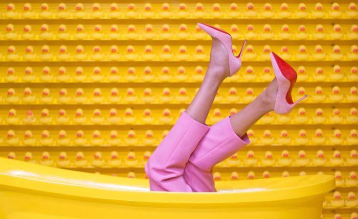 Femeie incaltata cu pantofi cu toc inalt de culoare roz si pantaloni de culoare roz
