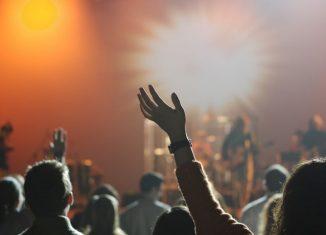 multime de oameni cu mainile ridicate la un concert
