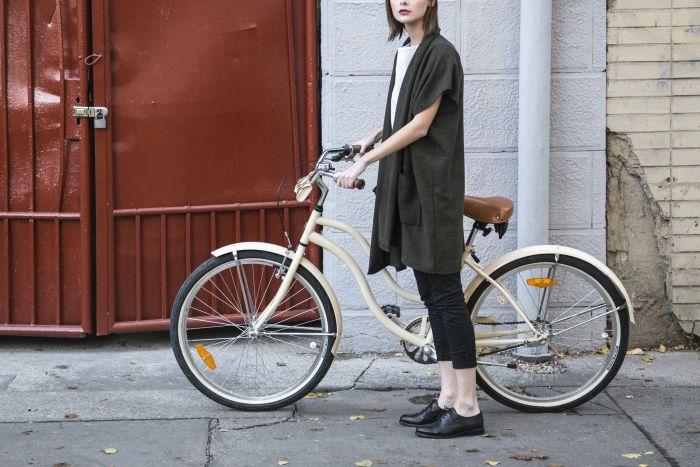femeie tanara care sta langa o bicicleta