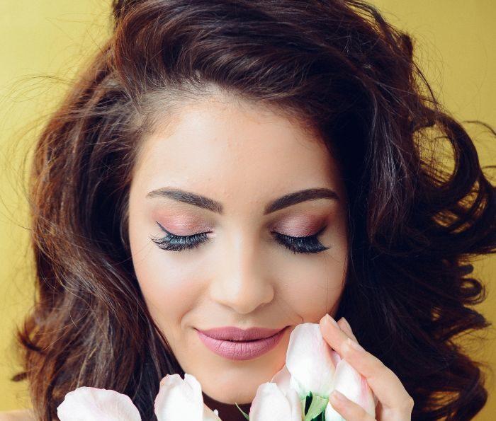 femeie cu gene false care zambeste si miroase un buchet cu flori