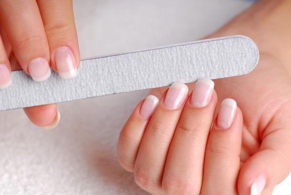 femeie care isi pileste unghiile