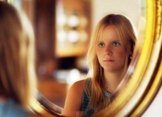 femeie blonda care se uita in oglinda