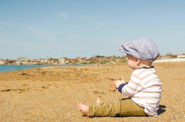 copil mic care sta in fundulet pe plaja