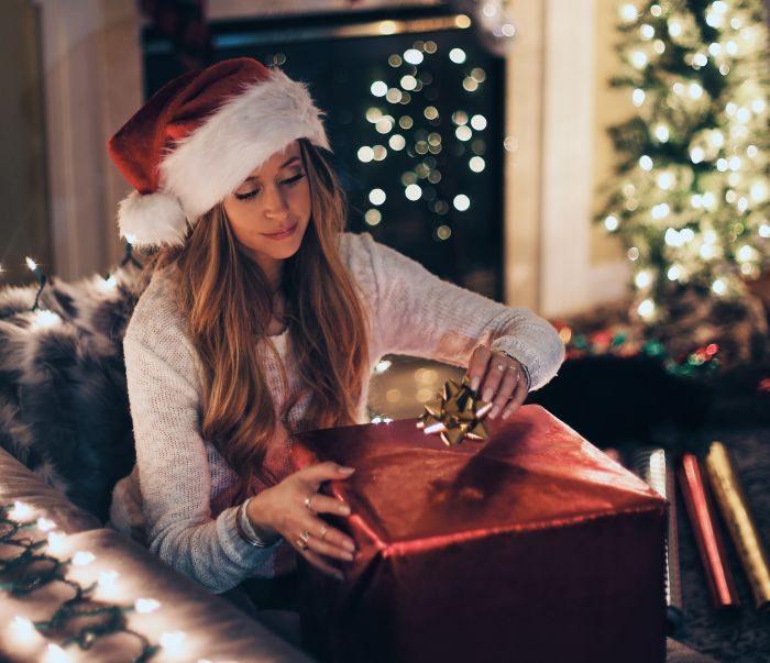 femeie care deschide un cadou de craciun
