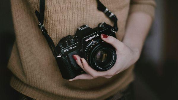 femeie care tine la gat un aparat de fotografiat
