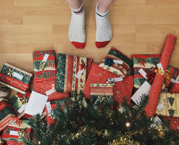 o persoana sta in picioare incaltata cu sosete langa mai multe cutii de cadouri de craciun