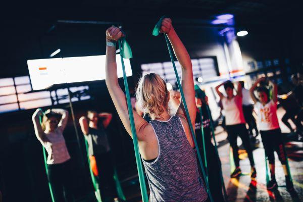 femeie la sala de fitness care se antreneaza cu grupul