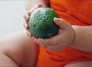 bebelus care tine in mana un avocado