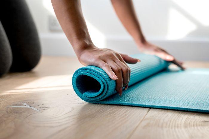 femeie care intinde o saltea ide yoga