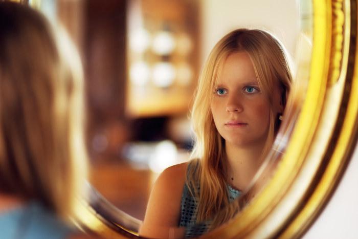 femeie suparata care se uita in oglinda