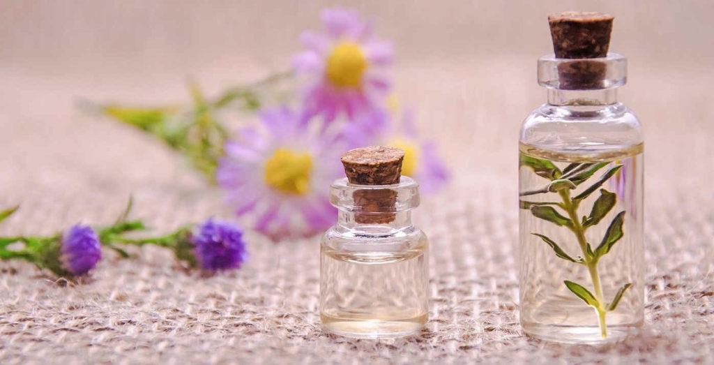Doua sticlute cu parfum langa flori mov și lila