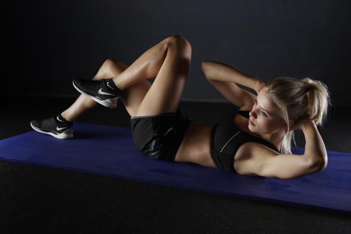 Femeie care face gimnastica de dimineață întinsă pe un covoraș și îmbrăcată în echipament sportiv